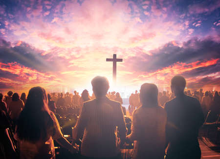 Worship concept: christian people hand in hand over cross on spiritual sky background 스톡 콘텐츠
