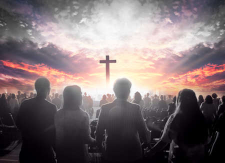 Worship concept: christian people hand in hand over cross on spiritual sky background 免版税图像
