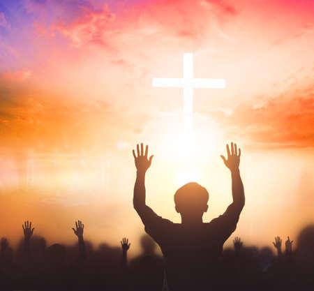 Worship concept: christian people Raise hand over cross on spiritual sky background Foto de archivo