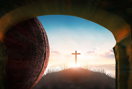 Easter concept: Tomb empty with cross on sunset background