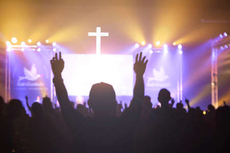 Church worship concept: Christian worship with raised hand at the at the cross cross background 스톡 콘텐츠