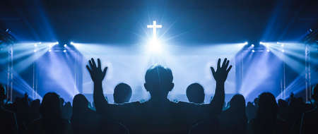 Church worship concept: Christian worship with raised hand at the at the cross cross background 免版税图像