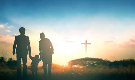 Family concept: Parents and children pray together on the cross background