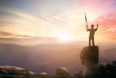 a disabled man standing up and raising his crutches over mountain sunset background 스톡 콘텐츠