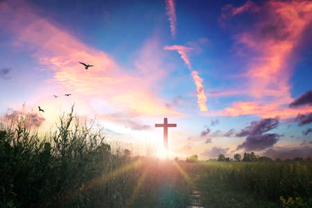 Easter concept: Concept: cross on sunset sky background 스톡 콘텐츠