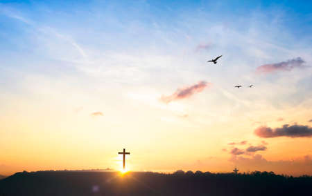 Silhouette cross on mountain at sunset