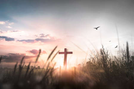 Easter concept: Silhouette cross on mountain at sunset background