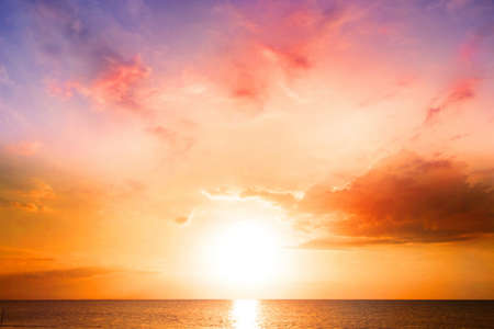 World Environment Day concept: Colorful ocean beach sunrise with deep Orange sky and sun rays
