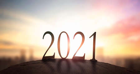 2021 concept: Silhouette of year 2021 on mountain with city sunset background