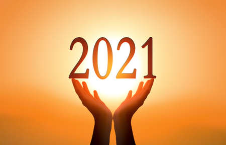 2021 concept: Hands hold 2021 against on sunset background
