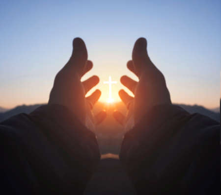 Religious concept: hands palm praying to cross in the sky 版權商用圖片