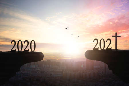 2021 concept: Silhouette of year 2021 and cross on mountain with city sunset background 版權商用圖片