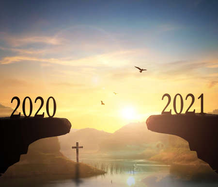 2021 concept: Silhouette of year 2021 and cross on mountain with sunset background 版權商用圖片