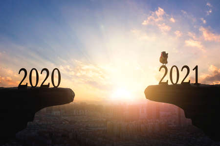 2021 concept: Silhouette of year 2021 and rooster on mountain with city sunset background 版權商用圖片