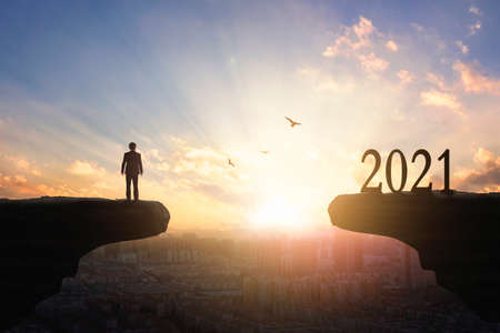 2021 concept: Silhouette of year 2021 and businessman on mountain with city sunset background