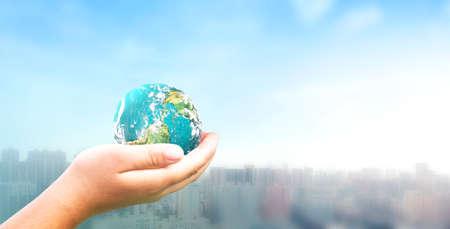 Human hand holding earth global over blurred city background. 版權商用圖片