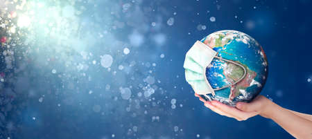 Hands Holding earth global In Abstract christmas lights background.