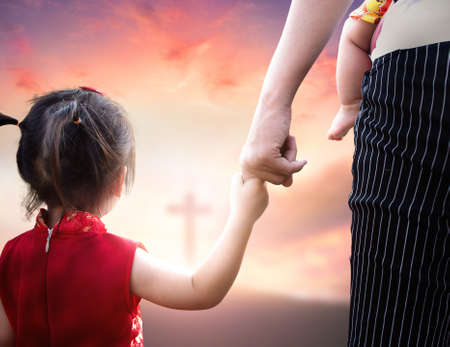 Child's hand holding mother's finger on blurred cross background.