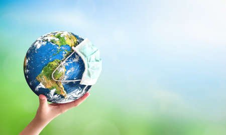 Earth day concept: human hand holding earth globe over blurred green and blue nature background.