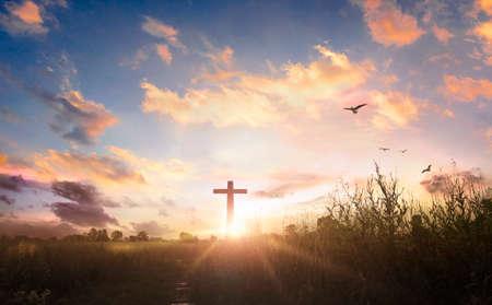 black cross religion symbol silhouette in grass over sunset sky background