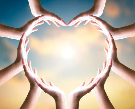 Unity and diversity partnership as heart hands in sunset sky background