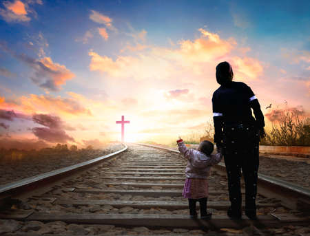 Praise and worship concept: Child's hand holding mother's finger on blurred The cross of jesus christ background.