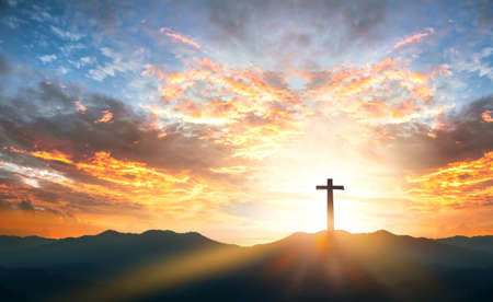 Religious day concept: Silhouette cross on mountain sunset background