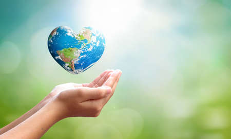 World environment day concept: man opens palms and drags heart shaped earth globe over blurred blue sky and water background. 스톡 콘텐츠