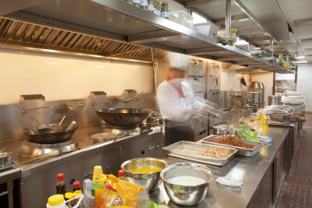busy restaurant: Chef cooking at commercial kitchen - hot job
