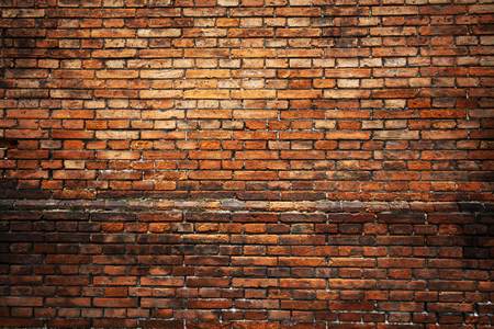 Red brick background: closeup of an old uneven brick wall. Archivio Fotografico