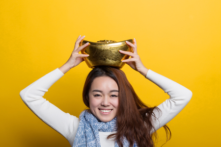 Yellow background, Chinese girl holding gold and blessing bag, Asian custom figure series Reklamní fotografie