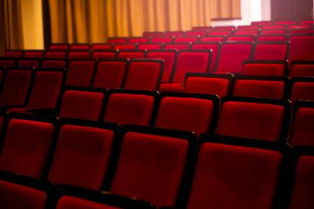 Auditorium in a theater or cinema, spotlights pass through empty seats