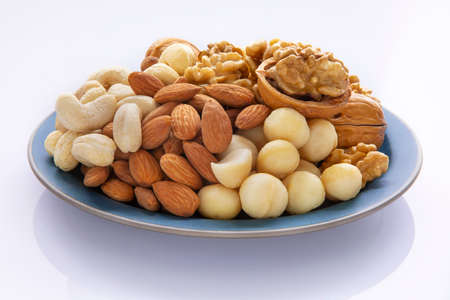 Nutritious mixed nuts on the plate, walnuts, almonds, cashews, macadamia nuts
