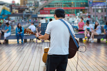 Street performer, Keelung Harbor, Taiwan, playing guitar and singing Stock Photo