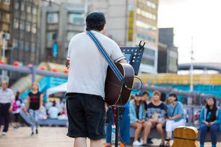 Street performer, Keelung Harbor, Taiwan, playing guitar and singing