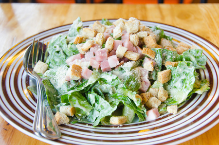A Caesar salad is a salad of romaine lettuce and croutons dressed with parmesan cheese, lemon juice, olive oil,egg and etc