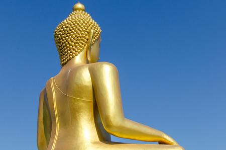Back side of golden buddha with deep blue sky background Banco de Imagens