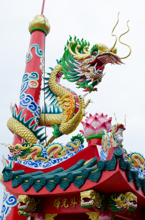 Dragon winding around the pole in chinese shrine in Thailand photo
