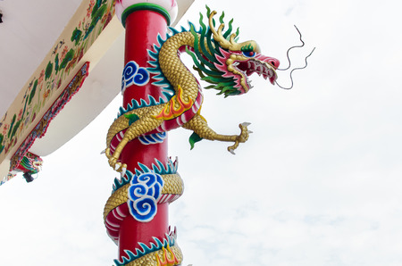 Dragon winding around the pole in chinese shrine in Thailand Banco de Imagens