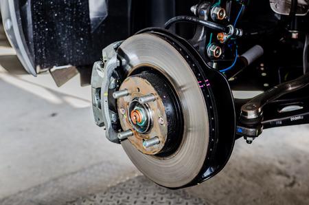 frenos: Freno de disco delantero en el coche en el proceso de sustituci�n de los neum�ticos nuevos. El borde se retira mostrando el rotor delantero y pinza Foto de archivo