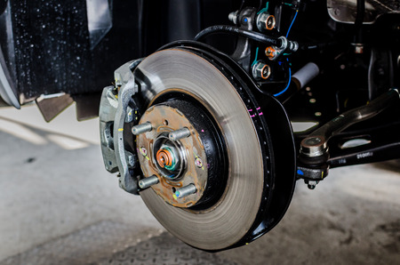 brake caliper: Front disc brake on car in process of new tire replacement. The rim is removed showing the front rotor and caliper