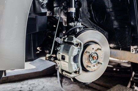 a round of inspection: Front disc brake on car in process of new tire replacement. The rim is removed showing the front rotor and caliper