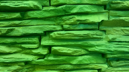 Background of green stone wall made with blocks.
