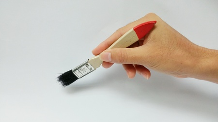 Man hand holding Paint Brush on a white background.(Natural lighting)