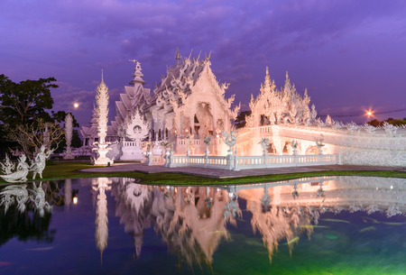 and the magnificent: Twilight of magnificent famous temple (Wat Rong Khun ) in Chiang Rai and water reflection