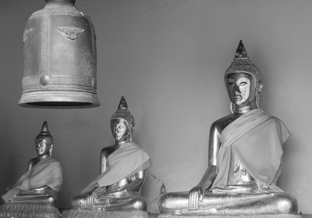venerate: Monochrome photograph of Metallic Buddha image and bell