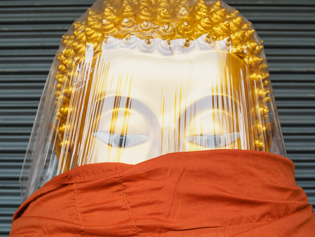 swaddle: Close-up Buddha image wrapped with clear plastic sheet and orange robe
