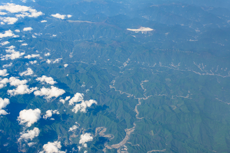 Small clouds floating above misty aerial view of mountain range Stock Photo