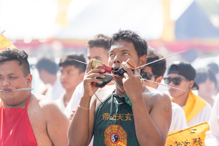 devotee: Nakhon Ratchasima, THAILAND - OCT 16 : An unidentified devotee of Vegetarian Festival, person who invites the spirits of gods to possess their bodies on October 16, 2015 in Nakhon Ratchasima, Thailand Editorial