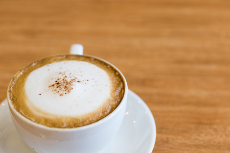 hot cappuccino on vintage wood desk background
